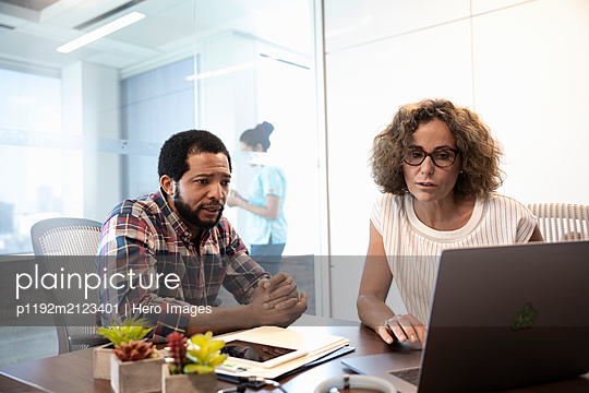 Medical consultant with laptop talking to mature man in hospital - p1192m2123401 by Hero Images