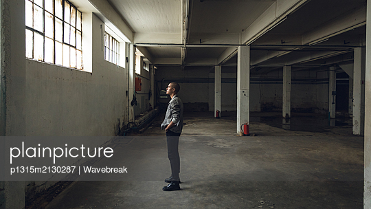 Young man inside an empty warehouse - p1315m2130287 by Wavebreak