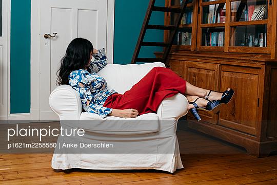 Woman relaxing in her living room - p1621m2258580 by Anke Doerschlen