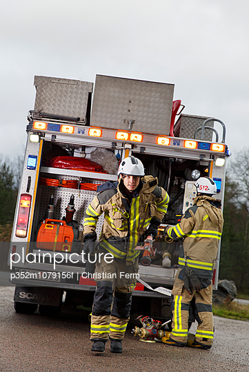 Sweden, Sodermanland, Tumba, Firefighter pulling hose from fire engine