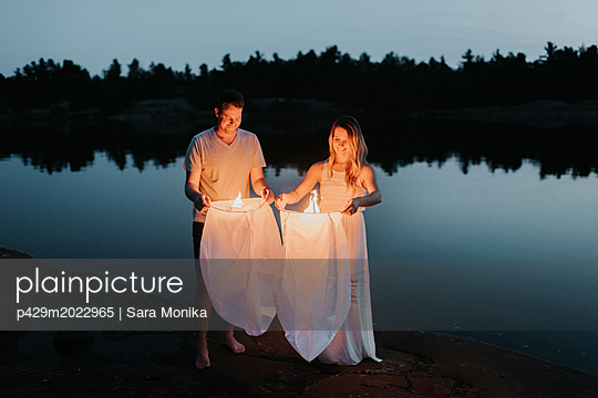 Couple releasing sky lanterns by lake, Algonquin Park, Canada - p429m2022965 by Sara Monika