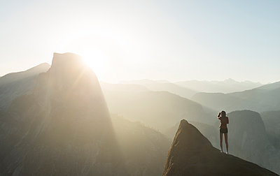 Rear view of woman standing on cliff at Yosemite National Park - p1166m1519095 by Cavan Images