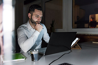 Businessman working on laptop in office at night - p300m1581019 by Uwe Umstätter