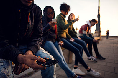 Friends using phone while sitting on railing at city square - p426m1179265 by Maskot
