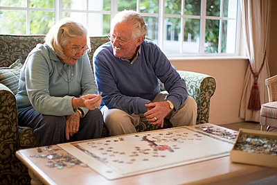 Older couple on sofa solving jigsaw puzzle - p555m1305745 by Resolution Productions