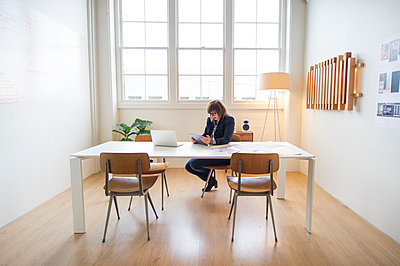 Businesswoman using digital tablet at desk in office - p555m1409652 by Shestock