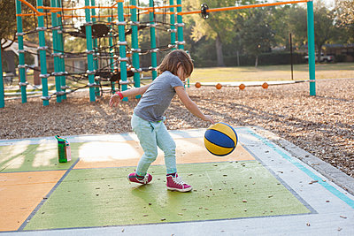 Girl bouncing basketball in playground - p924m1493724 by Kinzie Riehm