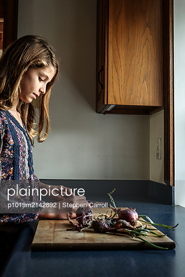 Girl cutting onions in the kitchen - p1019m2142892 by Stephen Carroll
