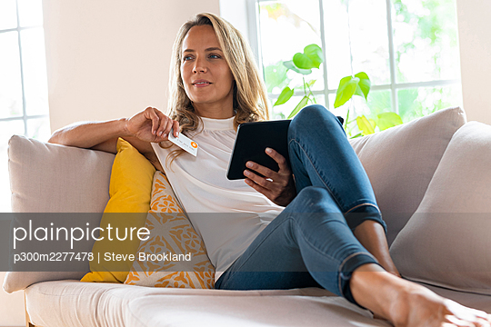 Beautiful woman with digital tablet holding bitcoin credit card while sitting on sofa at home - p300m2277478 by Steve Brookland