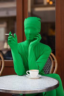 Person im Morphsuit raucht genüsslich im Café - p045m2016038 von Jasmin Sander