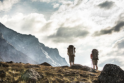 Low angle view of two backpackers on an alpine hillside - p1166m2190000 by Cavan Images