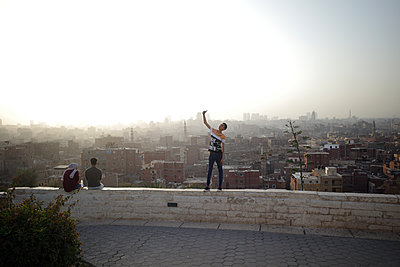 Young boy taking a selfie in front of Cairo city view - p1610m2181491 by myriam tirler