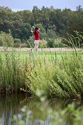 A female golfer teeing off - p30119779f by Halfdark