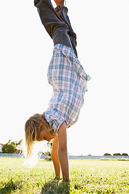 Girl doing handstand in park, side view - p31225660 by Elliot Elliot