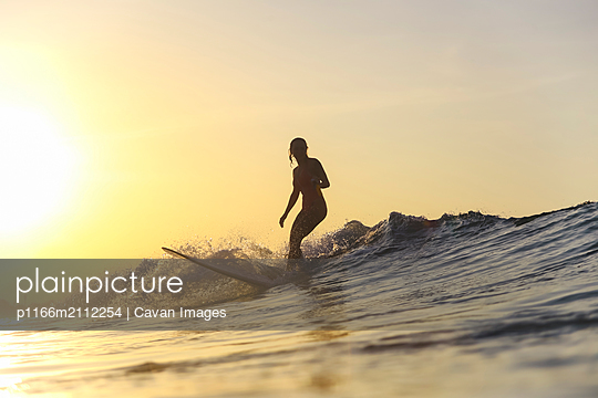 Young woman surfing at sunset - p1166m2112254 by Cavan Images