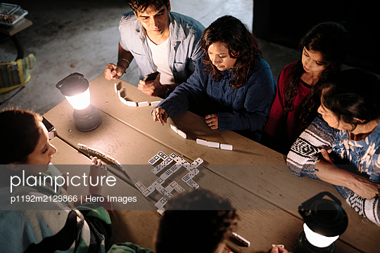 Indian family playing dominoes in log cabin by lamp light - p1192m2129866 by Hero Images
