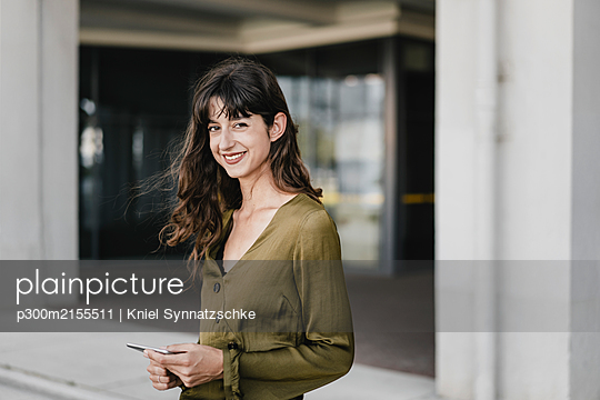 Portrait of smiling brunette woman holding smartphone - p300m2155511 by Kniel Synnatzschke