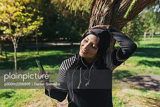 Smiling young woman taking selfie with smart phone while standing in park - p300m2206595 by Daniel Sierralta