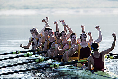 Rowing team celebrating in scull on lake - p1023m923594f by Chris Ryan