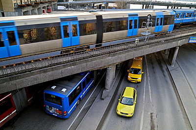 View of trains running on tracks on bridge with vehicles on asphalt road at Stockholm, Sweden - p1025m788973f by Peo Quick