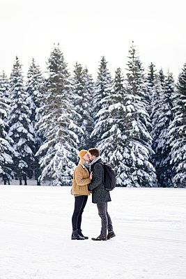 Young couple kisses in snowy landscape - p1124m1589316 by Willing-Holtz