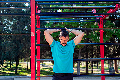 Brown guy with beard doing stretching on fitness bars in a park. - p1166m2268436 by Cavan Images