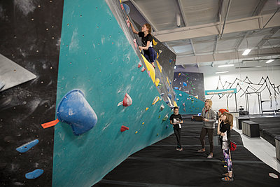 Female instructor and rock climbing students watching girl climbing wall at climbing gym - p1192m1560060 by Hero Images
