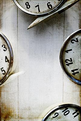 Four alarm clocks arranged on a white wooden floor - p1228m1123027 by Benjamin Harte