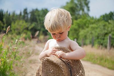 Blonder Junge hält einen großen Strohhut - p1685m2272469 von Joy Kröger