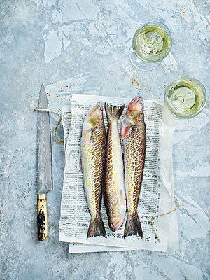 Knife and raw fish on newspaper - p312m2101897 by Matilda Lindeblad