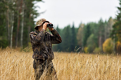 Teenager with binoculars watching forest - p312m798845 by Hans Berggren