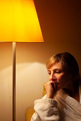 Nachdenkliche Frau mit Hand am Kinn sitzend neben einer Lampe - p795m2087462 von JanJasperKlein