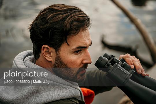 Handsome man with beard holding binoculars while looking away - p300m2286520 by Malte Jäger