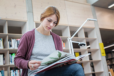 Female student leafing through book in library - p1284m1452028 by Ritzmann
