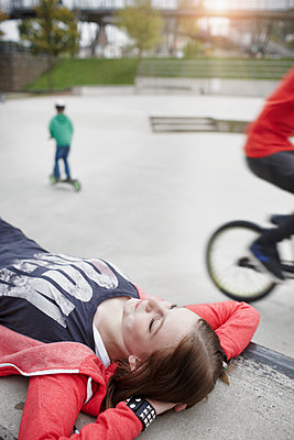 Teenage girl lying on a wall at a skatepark - p300m2104233 von Roger Richter