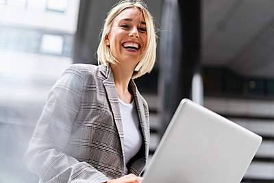 Portrait of happy young businesswoman with laptop in the city - p300m2143481 von Daniel Ingold