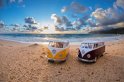 Two toy buses at beach during sunrise - p343m1570999 by Sean Davey