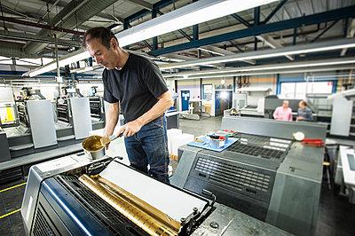 Worker applying gold ink to printing machine in print workshop - p429m884711f by Arno Masse
