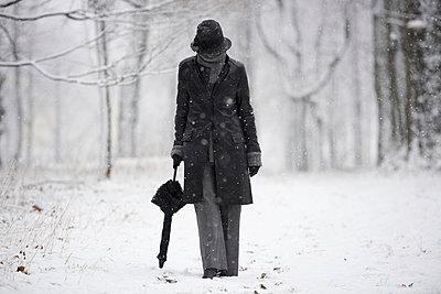 A woman walking down a snowy path in winter;Locarno ticino switzerland - p442m837659f by Mats Silvan