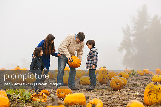 Parents with children examining pumpkins at farm during foggy weather - p1166m1416208 by Cavan Images