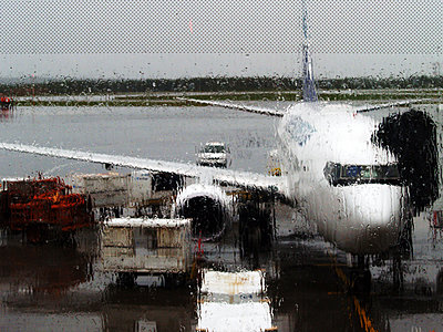Aeroplane on a runway viewed through a rainy window - p1072m828943 by Clive Branson
