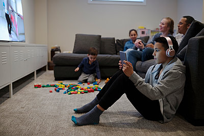 Family playing video game and watching TV - p1192m2094607 by Hero Images