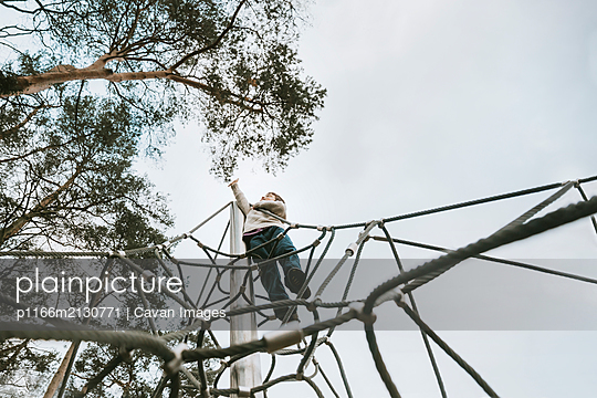 Low angle view of boy on climbing frame reaching for tall tree - p1166m2130771 by Cavan Images