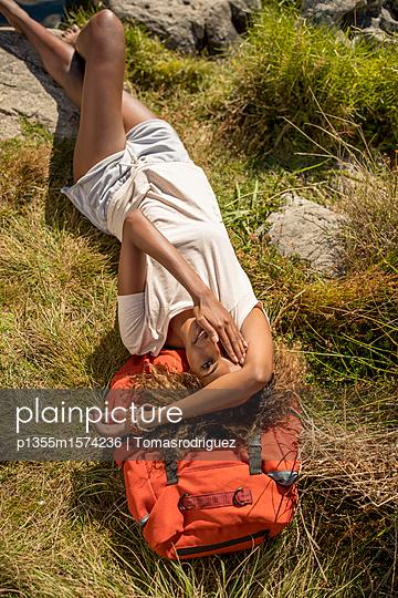 Junge Frau macht eine Pause beim Wandern - p1355m1574236 von Tomasrodriguez