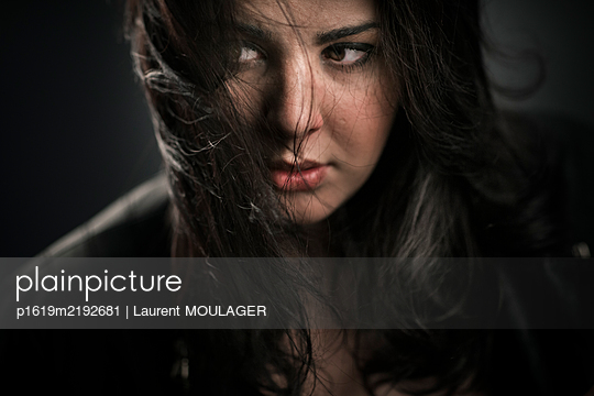 Portrait of a young brunette woman with round face - p1619m2192681 by Laurent MOULAGER