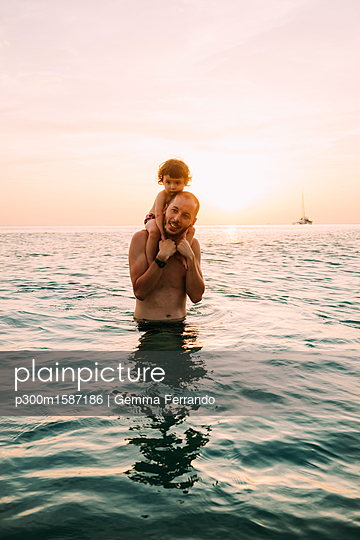 Father carrying his little daughter on shoulders in the sea by sunset - p300m1587186 von Gemma Ferrando