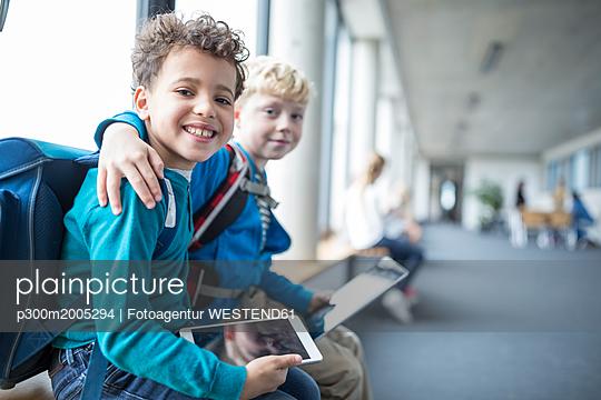 Portrait of two smiling schoolgboys with tablet embracing - p300m2005294 von Fotoagentur WESTEND61