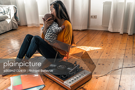 Mother with baby sitting on the floor at home with a record player - p300m2132419 by Richárd Bellevue