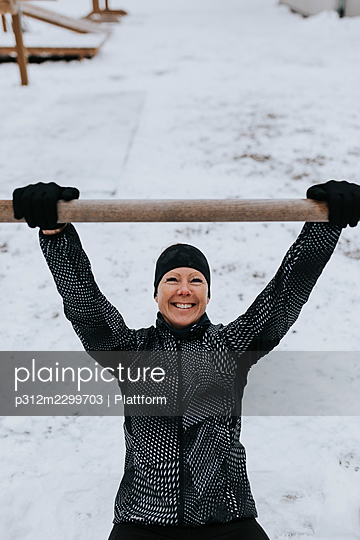 Smiling woman exercising at winter - p312m2299703 by Plattform