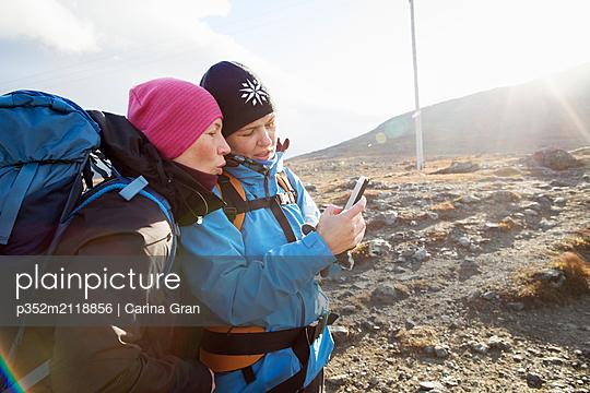 Women using smart phone during hike - p352m2118856 by Carina Gran